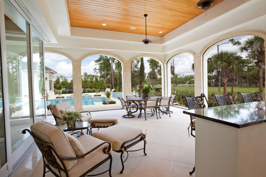 covered patio ideas this massive covered stone tile patio features a small bar in addition NOJMYVI