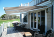 retractable awnings cream and brown striped awning extended over residential deck area JYSHBAR